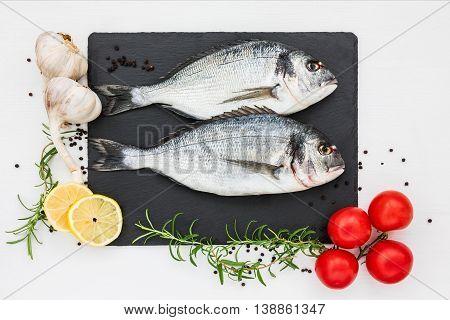 Fresh Dorado Fish On Slate Cutting Board, Rosemary, Garlic, Lemon And Tomatoes. Top View, Copy Space
