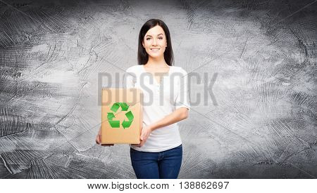 Woman with a paper box and recycle sign on it. Ecology, environment, and a world saving concept.
