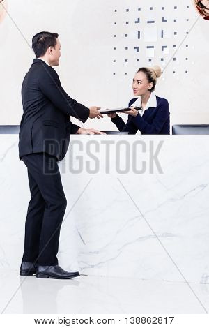 Job Applicant at business front desk giving his documents to receptionist