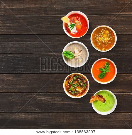 Variety of restaurant hot dishes, healthy food. Japanese miso, asian fish soup, russian borscht, english pea soup with bacon, mushroom soup, spanish gazpacho at brown wood, top view with copy space