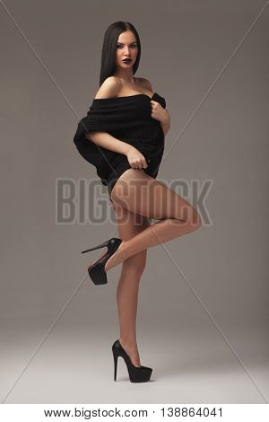 sexy brunette in a jacket standing on a neutral background fashion woman