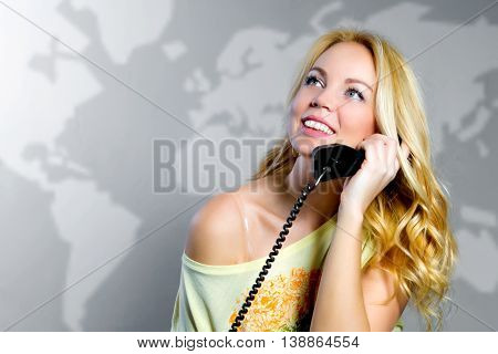 a pretty  girl with long fair hair is smiling and speaking over the telephone in the grey background