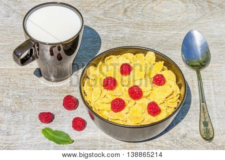 Breakfast in the garden on a sunny summer day. Bowl with corn flakes and raspberries mug with milk on a background grey wooden table