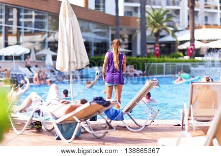 Summer holidays, people relax in the hotel poolside.
