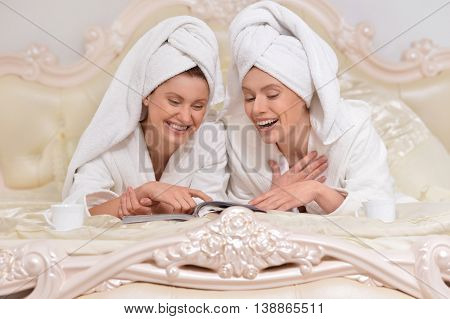 beautiful young women wearing a white bathrobe  reading magazine in bed