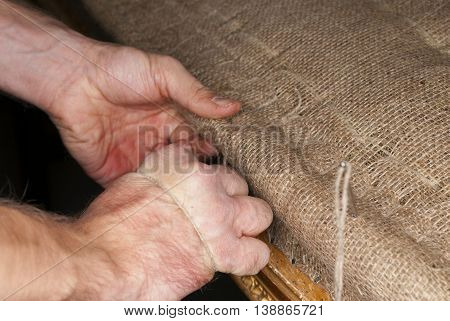 upholsterers hands restoring antique upholstery with traditional tools