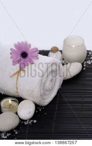 Spa resort -candle with gerbera daisy ,towel and stone on mat