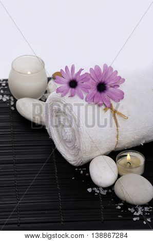 candle with gerbera daisy ,towel and stone on mat