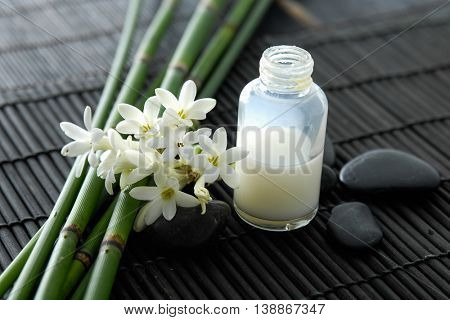 Tropical flower ,bamboo grove, stones, and oil on mat