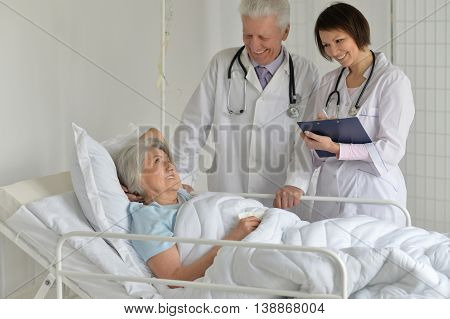 happy Senior woman in hospital with caring doctors