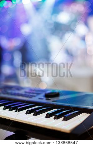 Piano Keyboard synthesizer closeup key frontal view, background of colored light