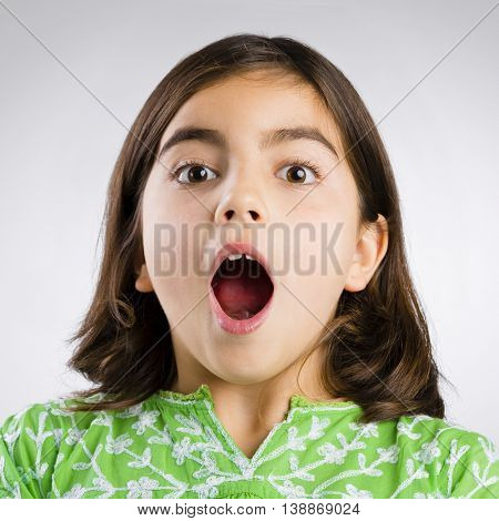 Portrait of a little girl making a astonished mouth expression