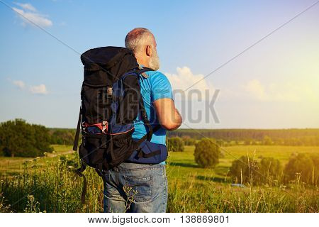 Back view of physically fit aged man with big rucksack standing in the rural area and looking into the distance