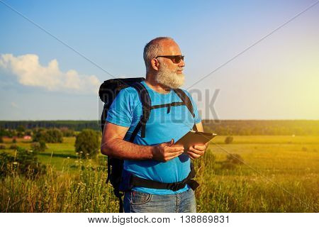 Handsome aged man in sunglasses with rucksack behind his back is standing in the field holding a data tablet in his hands