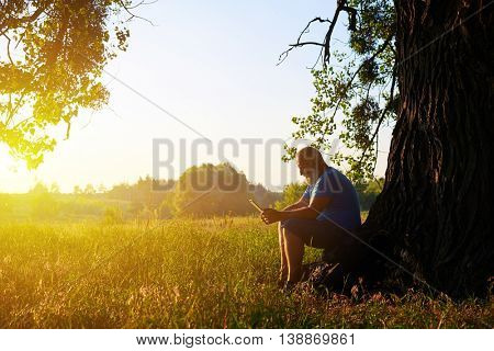 Aged man is sitting beneath a tree with his data tablet and enjoying the moment of relaxation on the background of beautiful summer sunset in the field