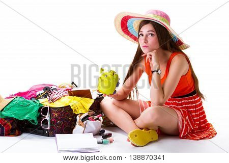 Girl sits near filled suitcase. Young lady holds money box. Feeling sad before departure. This money isn't enough.