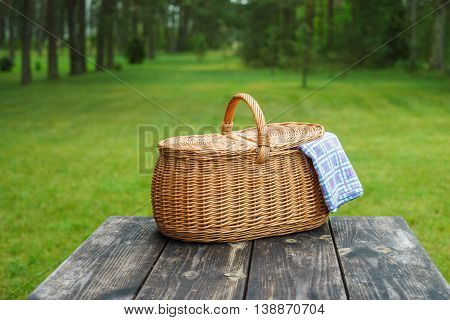 Picnic basket with blue white checkered tablecloth on wooden table. Summertime weekend break concept