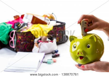 Hand with a piggy bank. Woman's hand holds dollars. Luggage and money for travelling. Save some money for later.