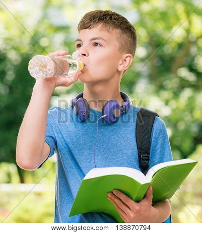 Teen boy 12-14 year old with bottle of fresh water and book. Student teenager with headphones and schoolbag posing outdoors.