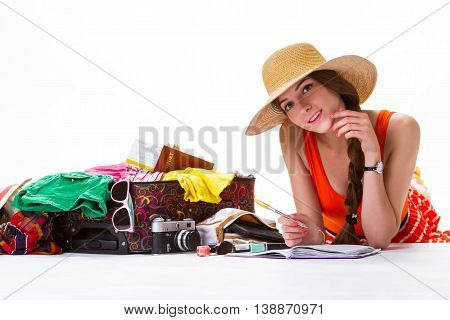 Girl lays near overfilled suitcase. Lady with notepad is smiling. Happy smile of young female. Enjoy every day of vacation.
