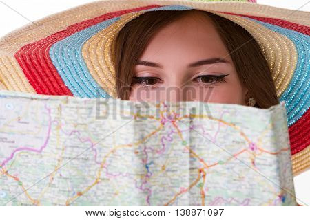 Lady's face behind a map. Young woman in striped hat. Plan your route carefully. Trip around the home country.