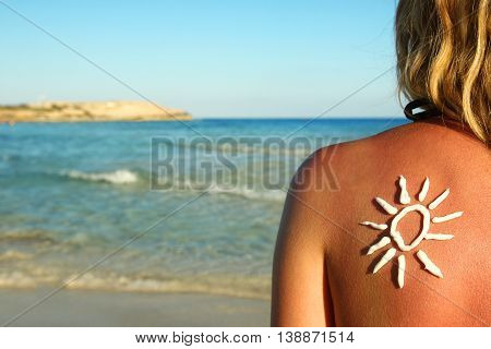 from sun cream on the female back on the seaside