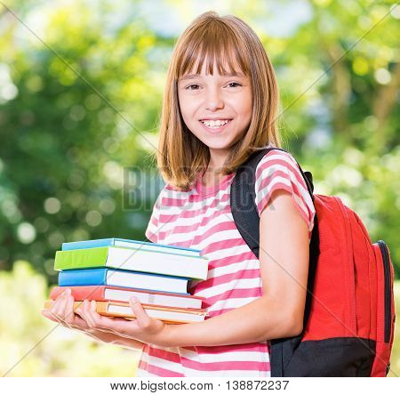 Outdoor portrait of happy girl 10-11 year old with books and backpack. Back to school concept.