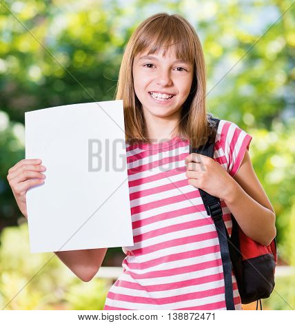 Outdoor portrait of happy girl 10-11 year old with white blank and backpack. Back to school concept.