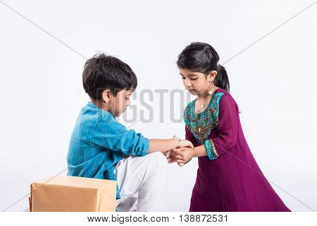 cute indian Sister tying Rakhi on her brother's wrist on the occasion of Rakshabandhan 0r raksha bandhan or Rakhi festival, isolated on white background