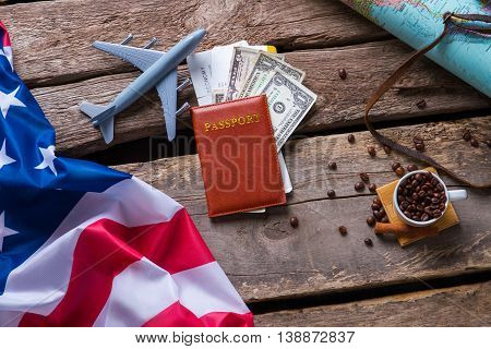 Passport near US flag. Toy plane and coffee beans. Journey to country of opportunities. New document on old table.