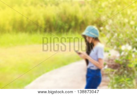de-focused young Asian woman in garden using a mobile telephone