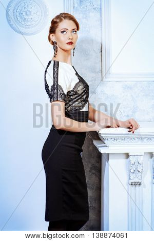 Beautiful smiling woman in elegant evening dress standing by a fireplace in a room with classical vintage interior. Jewellery. Fashion shot. Hairstyle.