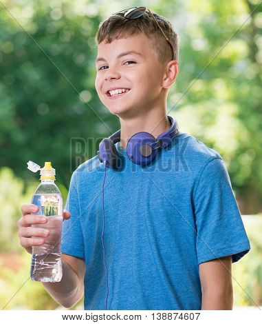 Teen boy 12-14 year old with headphones and bottle of fresh water. Student teenager posing outdoors.