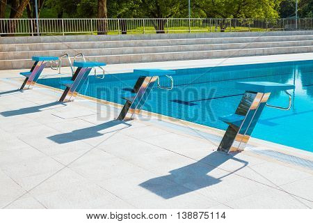 Starting blocks in a row at the edge of swimming pool outdoors. Selective focus. Swimming competition concept.