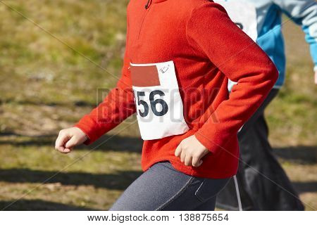 Junior female athletics runner. Cross country race. Outdoor circuit. Horizontal