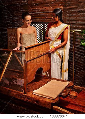 Woman having Ayurvedic sauna treatment. Exotic Indian sauna and masage.