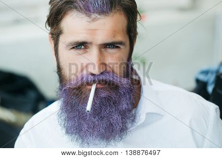 Sexy man with handsome serious face holding sigarette in his mouth with hair and beard colored in lilac dressed in white skirt outdoor