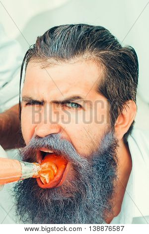 Young man with handsome face silver beard eating orange cream with open mouth on white background closeup