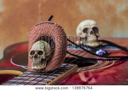 Skull top hat and guitar with classical background.