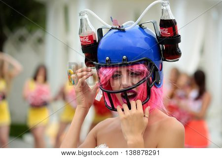 Ukraine Kyiv - July 28 2016: young patriotic sexy woman with pretty smiling face and pink hair in american football drink helmet with coca cola and lollipop celebrating independence day usa