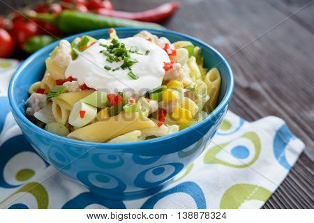 Penne pasta salad with fried chicken meat lettuce, red pepper, scallion and sour cream dressing