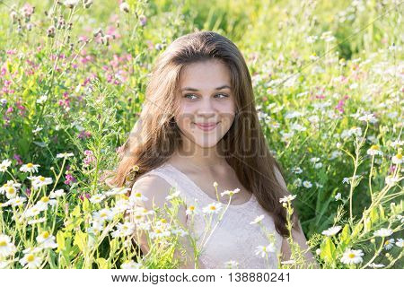 Thoughtful girl in a summer dress in a meadow