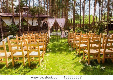 Beautiful wedding ceremony in the park. Wedding arch and chairs