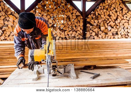 Carpenter working. Man using circular saw to cut planks of wood for home construction