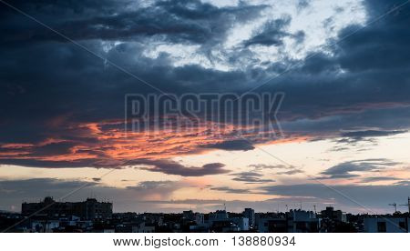 Dramatic stormy sky with red and blue clouds just before the sunset above the city of Nicosia Cyprus
