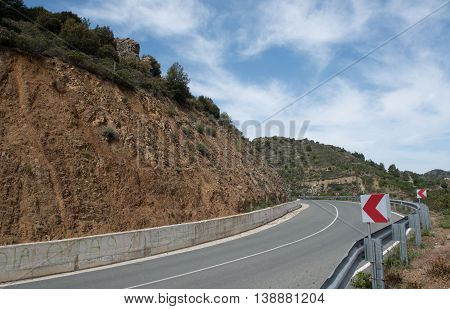 Empty Curved mountain asphalt road with directional red signs and dangerous blind curve at Troodos mountains in Cyprus