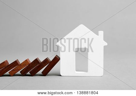 Dominoes and wooden house shape on grey background