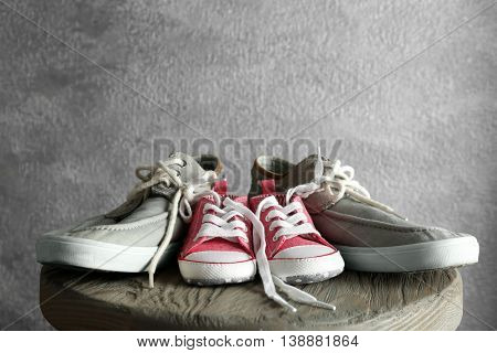 Big and small shoes on wooden stool