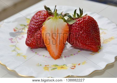 Several fresh strawberries  lying in a saucer.