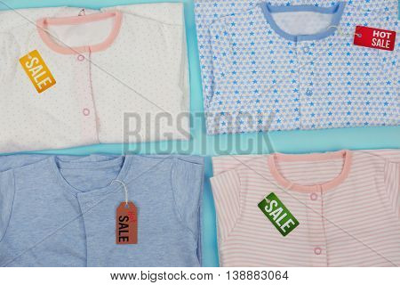 Baby clothes and tags on color background. Sale concept